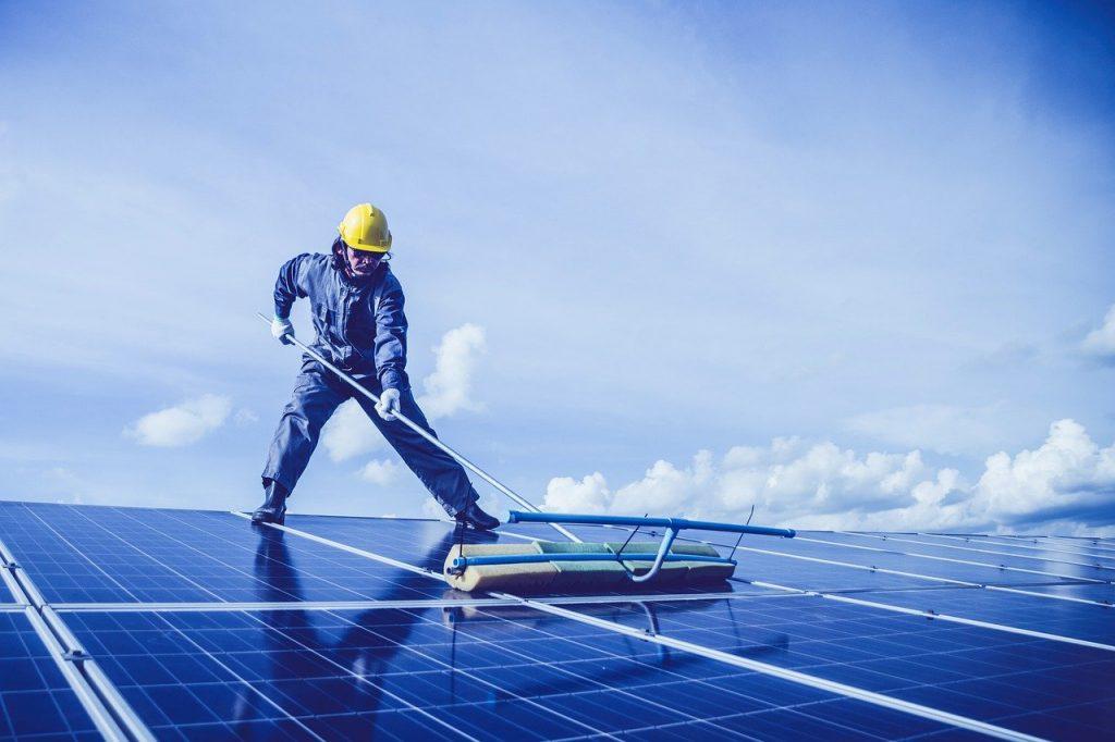 homme nettoyant des panneaux solaires