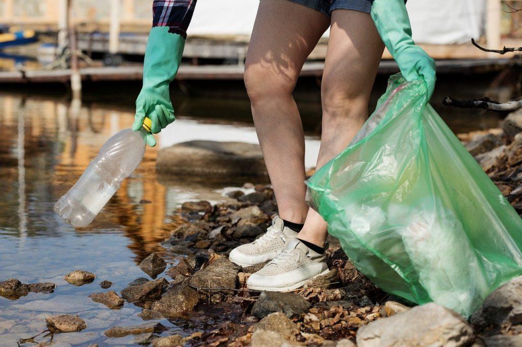 personne qui ramasse des déchets de bouteille plastique